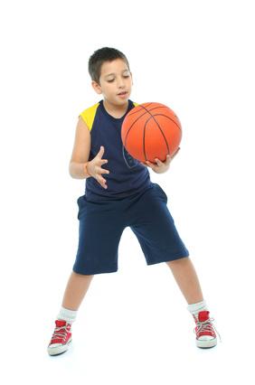 Boy practicing basketball skills alone
