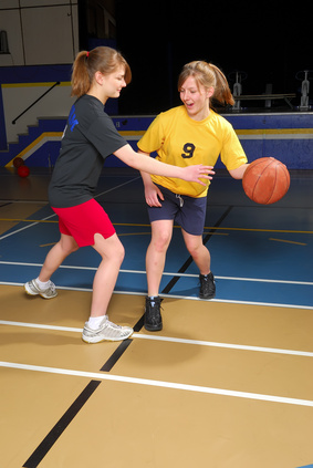 Two girls enjoying playing basketball